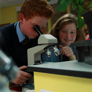 Boy and girl looking through microscope in science class